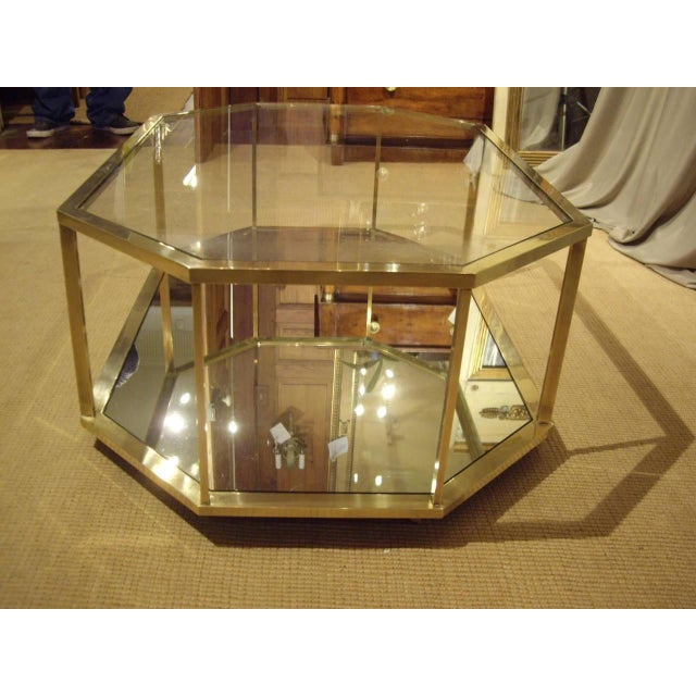 Unusual shaped French vintage brass coffee table. Glass top and shelf. Circa 1960.