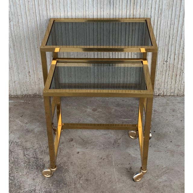 About Pair of Italians nesting tables, brass in original patina and glasses in perfect conditions, they are on wheels....