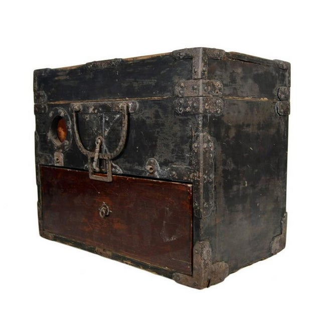 An antique handmade Chinese money box with metal hardware from the 19th century. This rectangular box is made of two-tone...