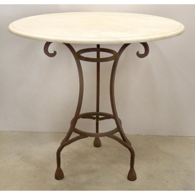 Offered for sale is a wrought iron bistro table fitted with a honed stone top. The iron frame is rustic in nature and...