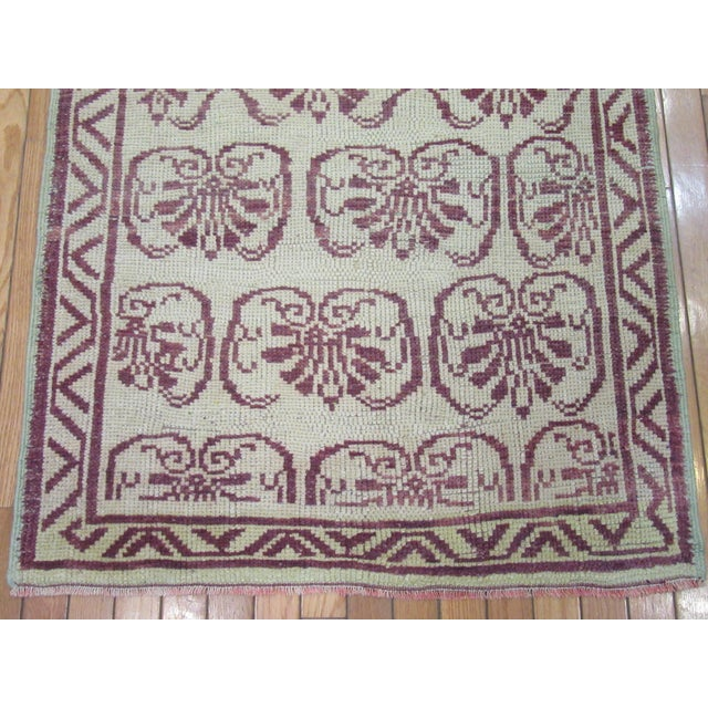 This is a vintage hand knotted wool short runner rug from Turkey. It has an allover floral design in burgundy color on an...