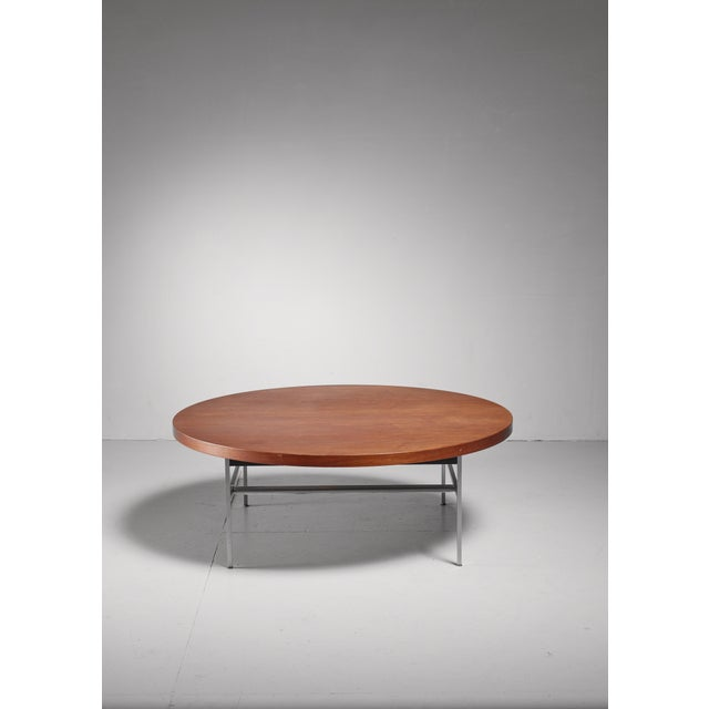 A large and heavy, round coffee table by George Nelson for the Herman Miller company. The walnut top rests on an aluminum...