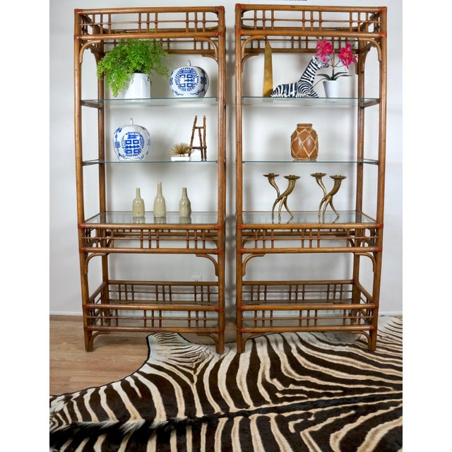 Great pair of McGuire style etageres. Dark rattan with wrapped leather detail. Each shelving unit has 4 glass shelves....