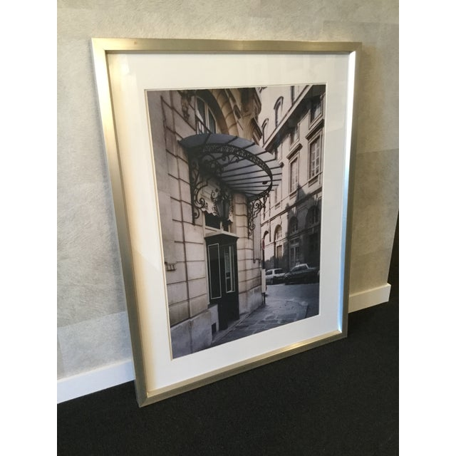 Photograph of a Paris street awning by artist Soicher Marin. Photo is framed in a brushed silver frame with white matting....