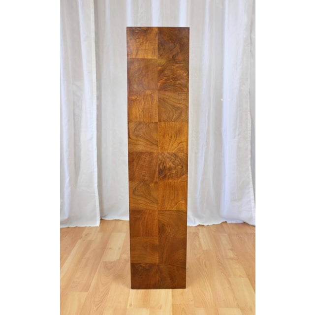 A circa-1970s tall walnut pedestal in the style of Milo Baughman. Finished on all sides in lively figured crown cut walnut...