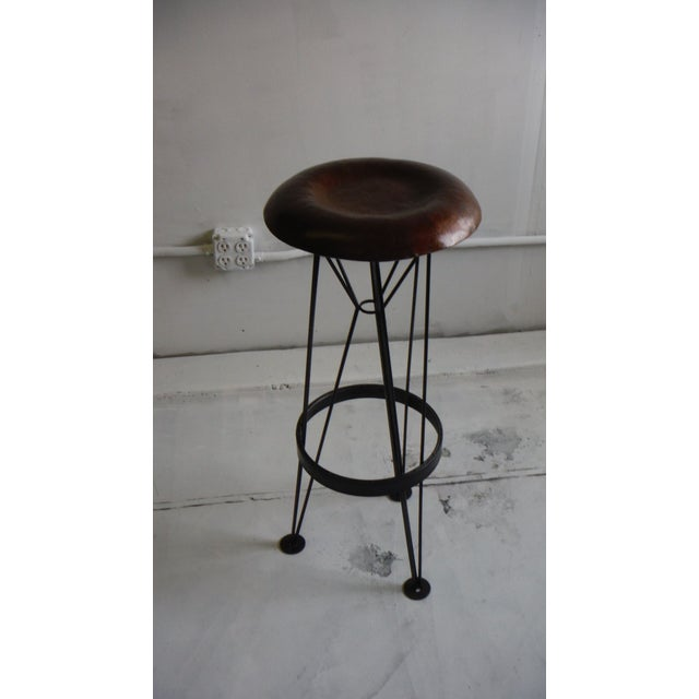 A light steel tripod supports a hammered sheet steel seat. Beautifully textured using vintage automotive forming...