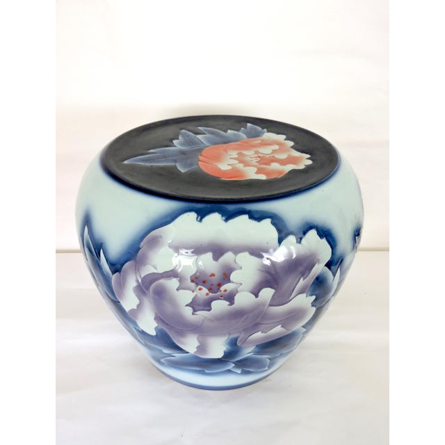 Contemporary in style - a ceramic drum stool or garden seat decorated with large coral/red and purple/lilac peony flowers...
