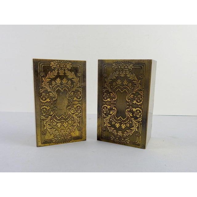Pair of vintage brass bookends, etched in classical renaissance design. Flat L shape, overall patina, some scuffing.