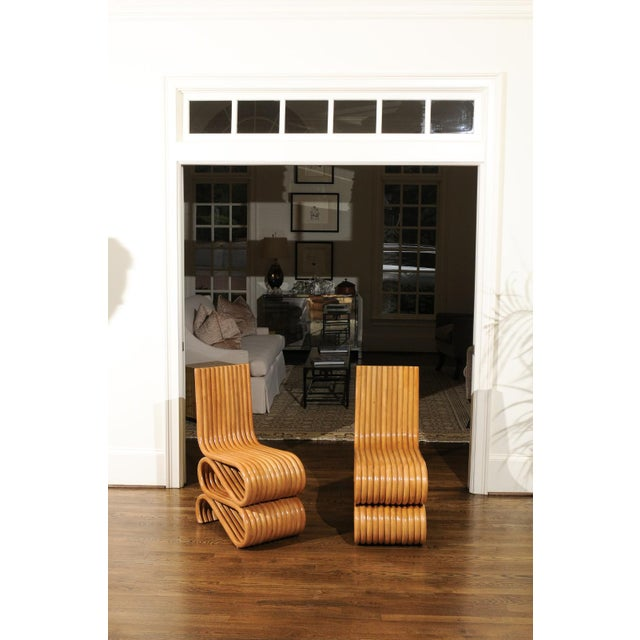 A unique set of eight stunning custom made dining chairs, circa 1995. This particular rattan design was undoubtedly...