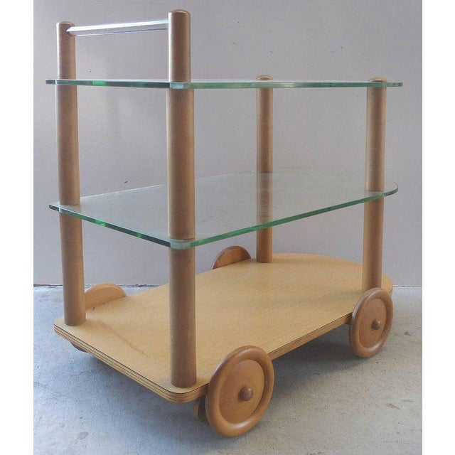 Offered for sale is a 1940s bar cart by Gilbert Rohde in oak with glass. The two-tier cart has overscale wood wheels with...