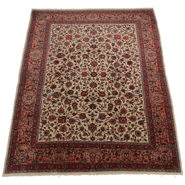 Here is a Persian Mashad rug of great size. Made of hand-knotted wool. Features a floral design.