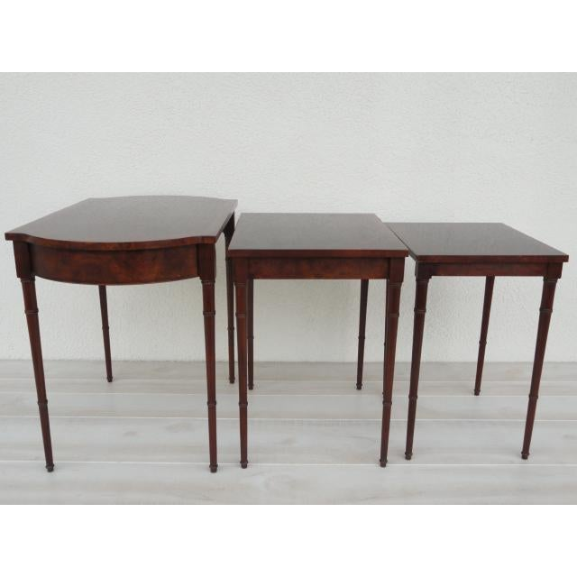 Three dark mahogany wood Baker Furniture nesting tables with bamboo style legs. The largest table of the three has a...