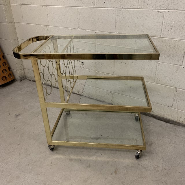 Fantastic brass bar cart ready for the holidays! 3 tiered shelves and space for 8 wine bottles! Rolls easily and is very...