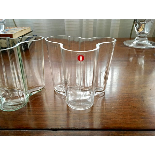 Pair of Alvar Aalto blown glass wave-shaped vases, one colorless and one with a slight green tint, as pictured. One has...