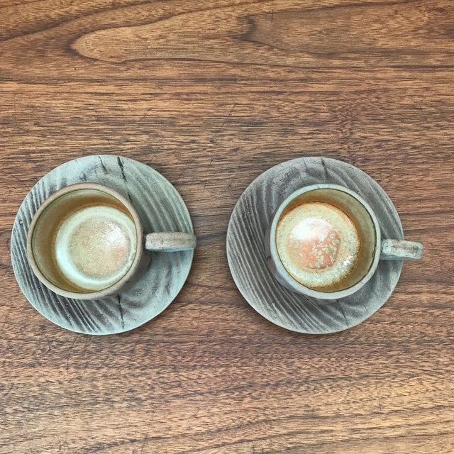 Pair of vintage pottery mugs with matching saucers. They ressemble wood or tree bark, though are unglazed pottery on the...