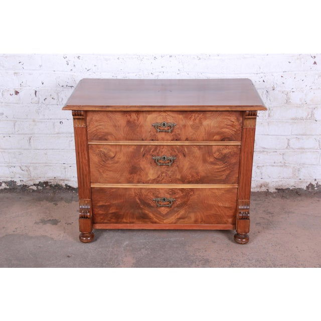 A beautiful 19th century Continental burled walnut chest of drawers. The dresser features stunning flamed walnut wood...