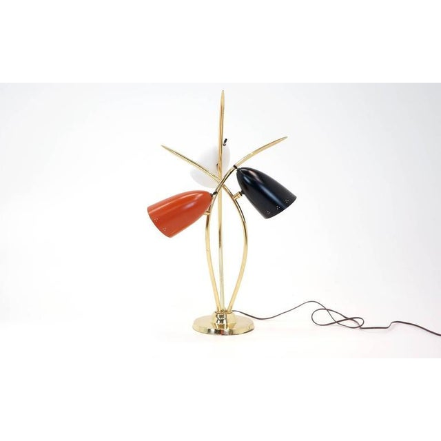 """Three arm Lightolier table lamp with red black and white conical shades. Base diameter: 7.5""""."""