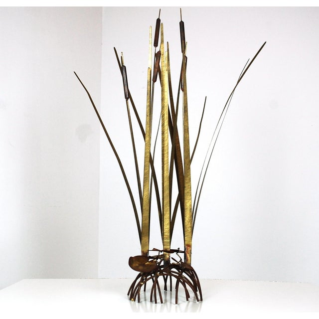 Life size Cattail Sculpture. Brushed brass leaves float above torch-cut lily pads to create a floor-standing sculpture...