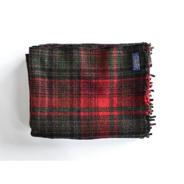 A vintage Pendleton Woolen Mills 100% virgin wool plaid blanket, in a tartan pattern of red, black, and green.