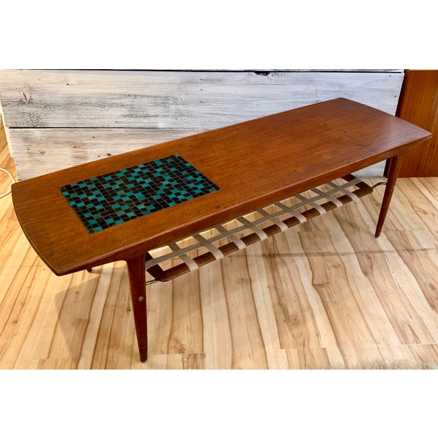1960s Danish Modern teak coffee table by Arne Hovmand-Olsen for Mogens Koch. This table features a striking black and teal...