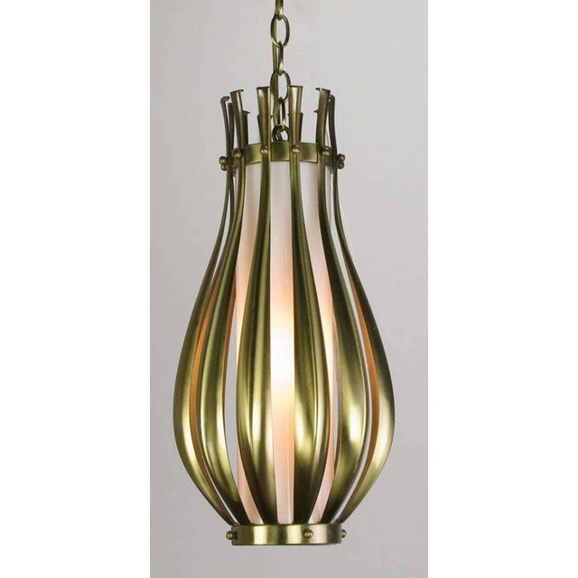 Ribbed and brushed brass gourd form pendant hanging light fixture, with a milk glass internal shade. Detailed with brushed...