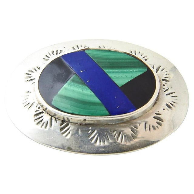 Black onyx, malachite and lapis inlaid into an oval sterling silver brooch. The raised inlaid section is surrounded by a...