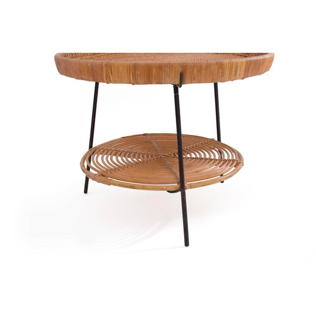 Wicker and iron occasional table by Raymor, circa early 1950s. This all original example is two-tiered with both sections...