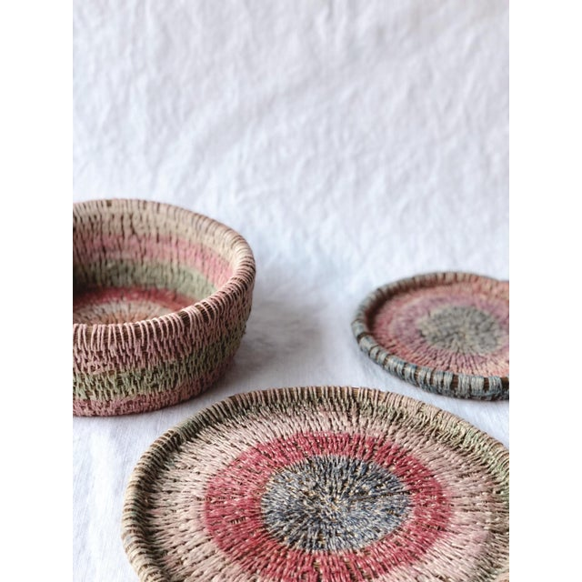 These beautiful plates/baskets are painstakingly made with pine needles and woven, colorful string. They even smell of...