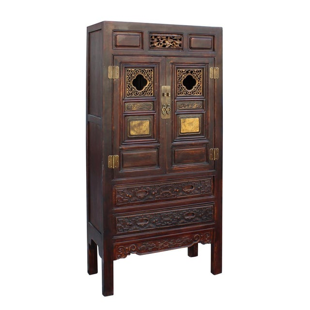 This is a brown base color Armorie wardrobe storage cabinet in oriental Fujian style which has carving and golden color...