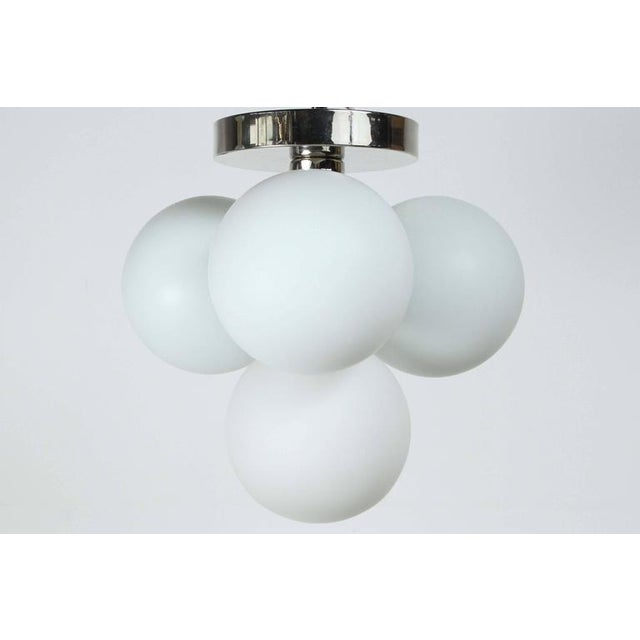 Pair of 1970s Globe sconces / flush mounts. Each polished chrome fixture has four white glass globes which are each...