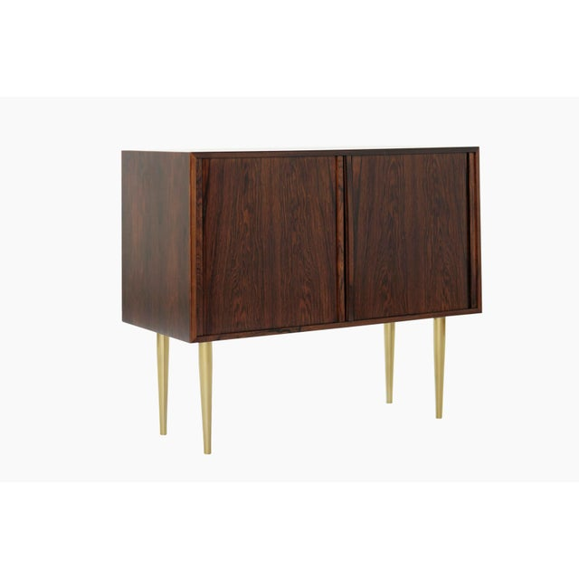 An exceptional cabinet made from rosewood, featuring tambour doors and brass legs.