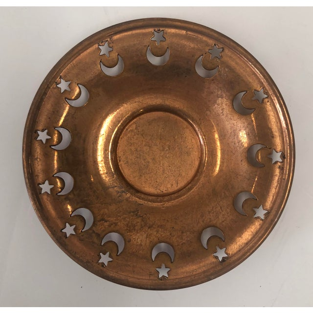 Set of ten matching copper votive or tea candle holders. Each one has a repeating pattern around the rim of the dish. Each...