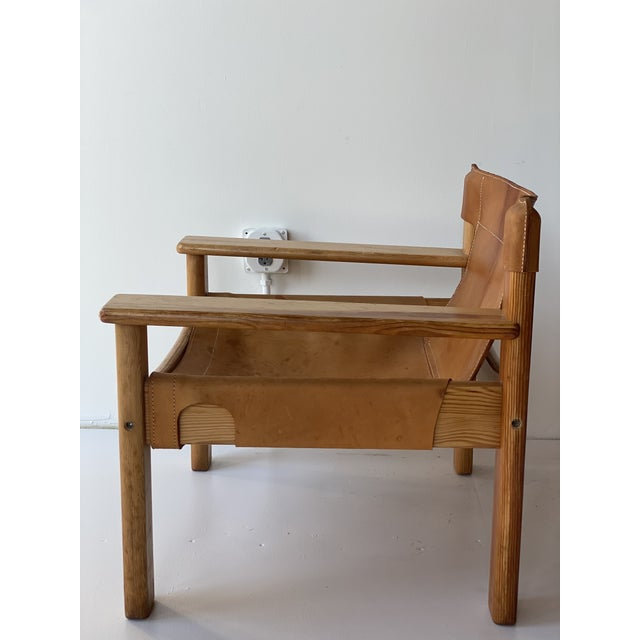 Iconic design 1970's safari chair in softly tanned saddle leather and solid pine wood frame. Nice patina. Karin Mobring...