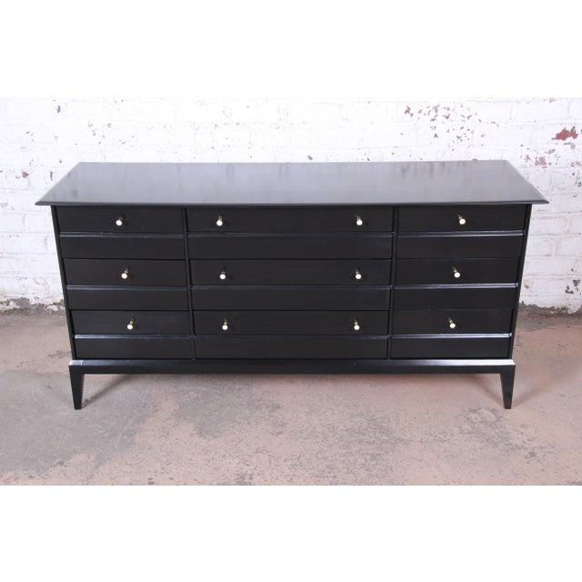 A gorgeous mid-century modern triple dresser or credenza by Heywood Wakefield. The dresser features a newly ebonized...