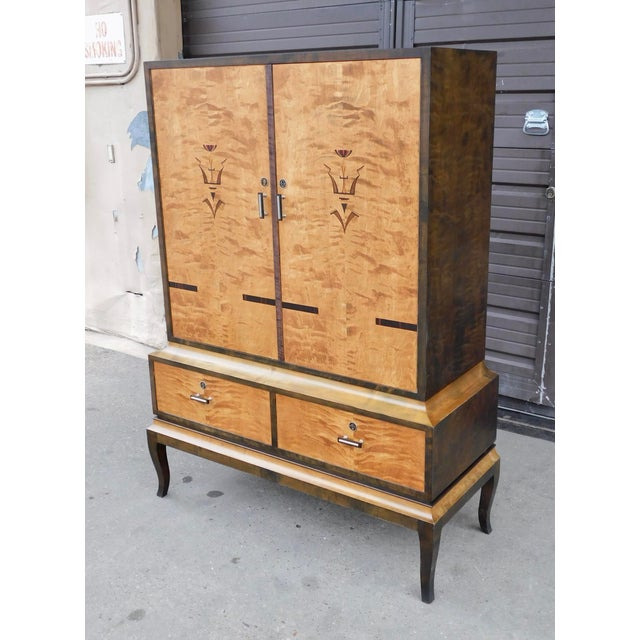 Swedish Art Deco inlaid storage cabinet rendered in birch wood. With doors in highly figured bookmatched birch wood....