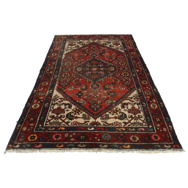 Crafted of hand-knotted woo, this Persian Hamedan rug features a geometric design.