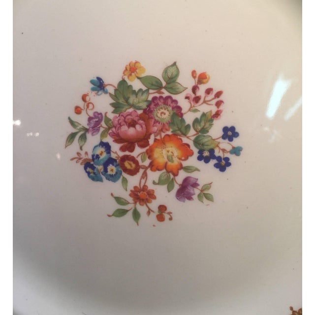 Vibrantly colored floral service plates with blue scaled borders and floral cartouches. Marked on the back, Alfred Meakin....