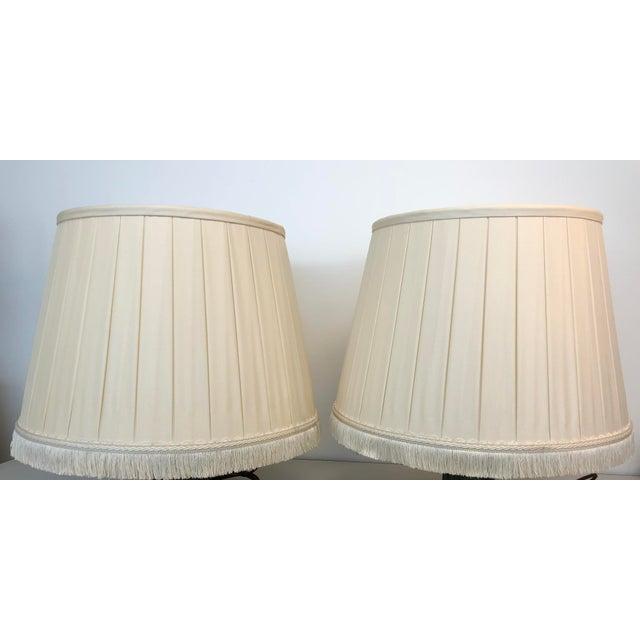 """A pair of box pleated traditional custom Paul Ferrante cream color shades with fringe detail at the bottom. 14"""" Top x 19""""..."""