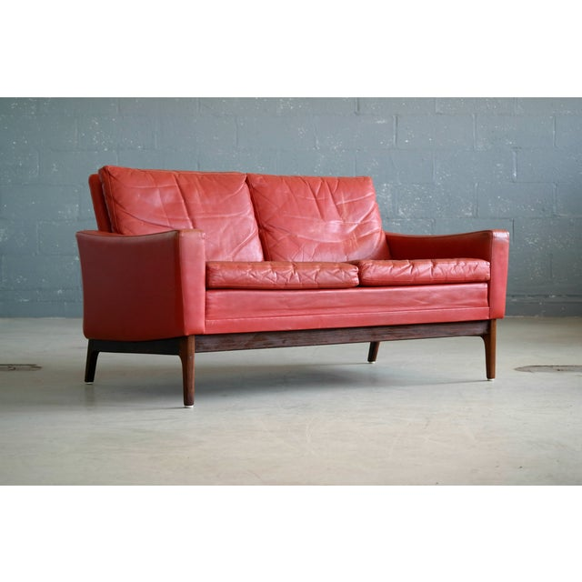 Very elegant classic mid-century Danish sofa in nice red leather on a beautiful rosewood base. Likely made in the 1960's...