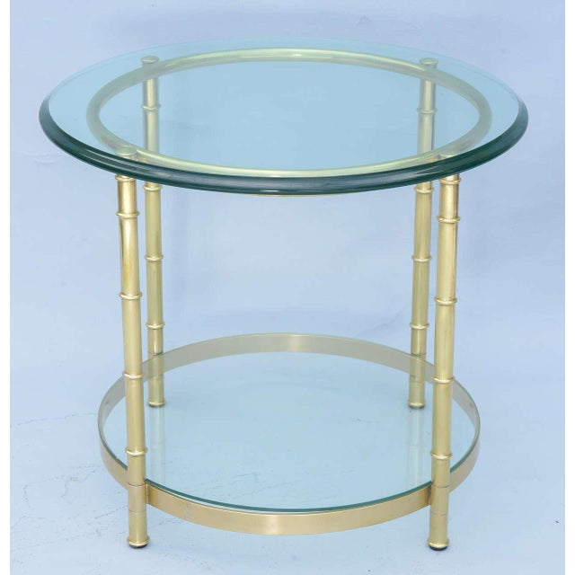 End or side table, of polished brass, its round glass top raised on faux bamboo legs, joined by ring apron and shelf-...