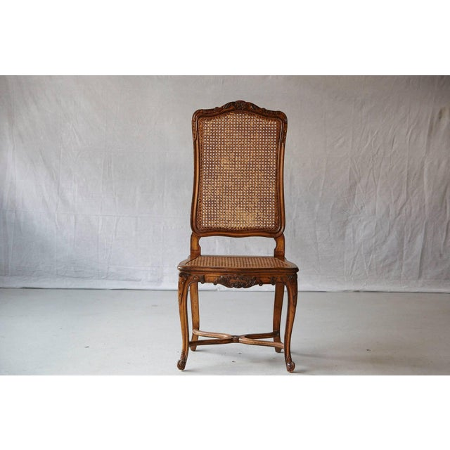 Lovely 19th century walnut high back chaise with caned back and seat. Carved knee mounts and blossom cresting, raised on...
