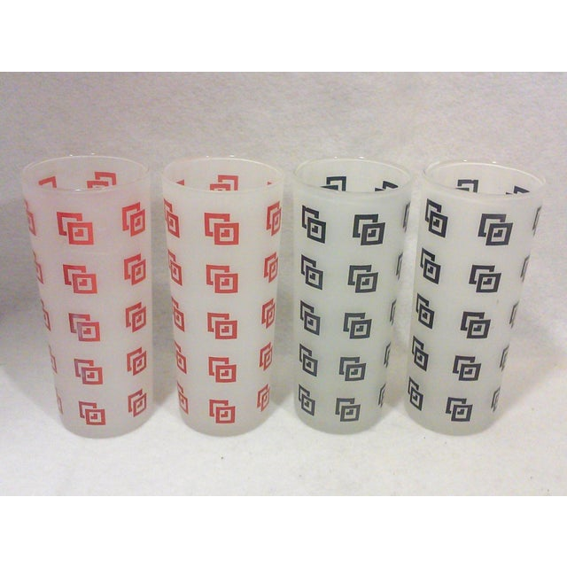 A set of four frosted glass Tom Collins bar glasses with a red and black geometric design. All of these cool glasses are...