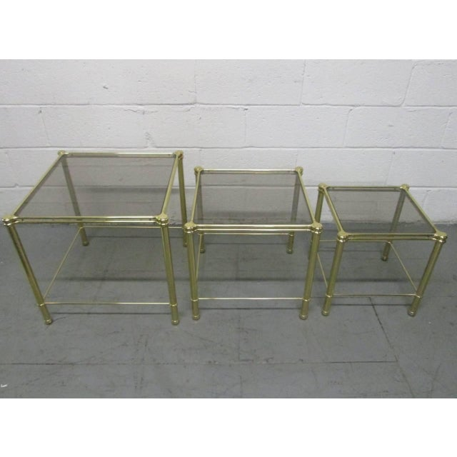 "Nesting tables with a decorative brass frame and smoked glass tops. Larger tables measures: 19.25"" H x 20.75"" W x 20.75"" D."
