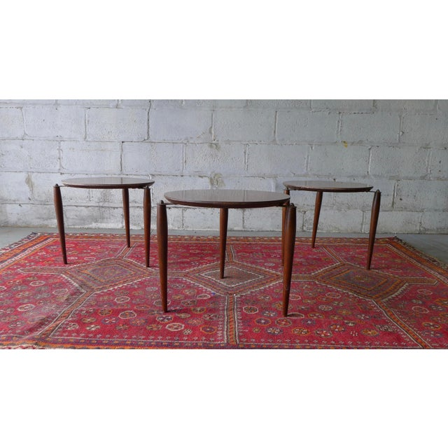Mid century modern stackable trio of plant stands or end tables. Round wooden tables with laminate tops and wooden tapered...