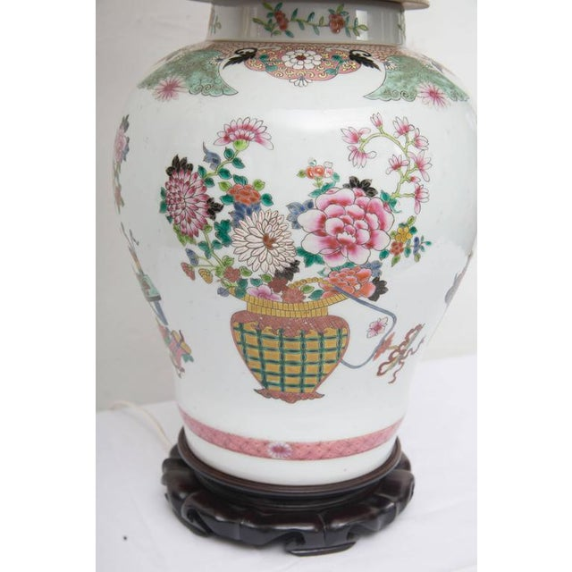 This lovely pair of Chinese lidded urns are painted with baskets and floral sprays affixed to hand carved scalloped bases,...