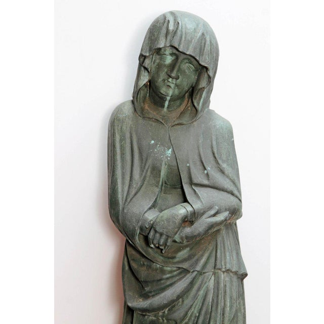 A bronze statue of a shrouded woman. The figure has a downcast pensive gaze and crossed hands reflecting a mood of...