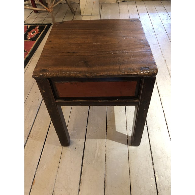 A handsome almost square rustic wooden Chinese end table having irregular shaped edges with wonderful character and a dark...