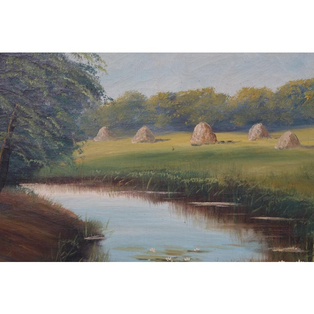 Mid-Century landscape featuring a scenic view of a small river/creek near between a patch of woods and a pasture of hay...