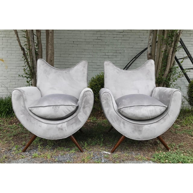 A glorious pair of sculptural lounge chairs in the style of Jean Royere. Modeled after the famed designer's most sought...