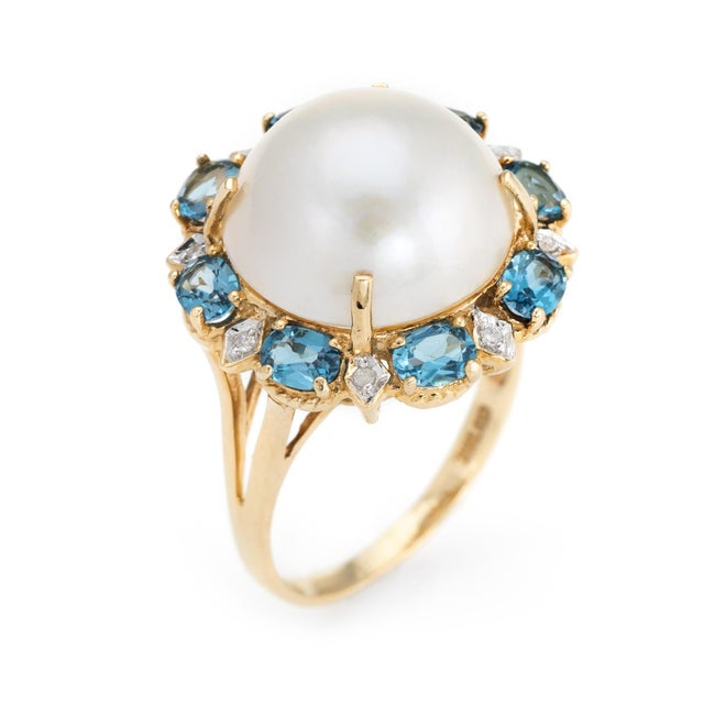 Finely detailed mabe pearl cocktail ring, crafted in 14 karat yellow gold. Centrally mounted 14.5mm mabe pearl is accented...